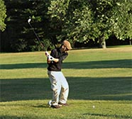 A golfer swings his club at the ball on a tee on a golf course.